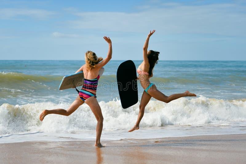 Gesunde athletische SurferFreundinnen mit den Sitzkörpern, die bodyboards halten stockfotografie