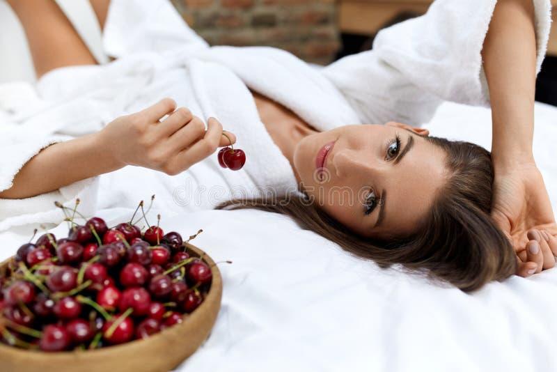 Gesunde Diät-Lebensmittel für die Gesundheit der Frau Mädchen, das Früchte auf Bett isst stockfotos