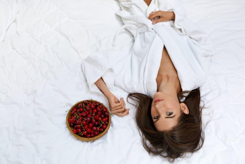 Gesunde Diät-Lebensmittel für die Gesundheit der Frau Mädchen, das Früchte auf Bett isst stockbild