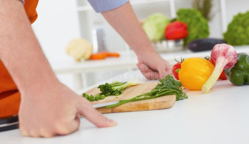 Gesunde Ernährung, Kochen, vegetarisches Lebensmittel, oben nährend und Leutekonzept - nah vom Mann, der Frühlingszwiebel mit Mes stockfoto