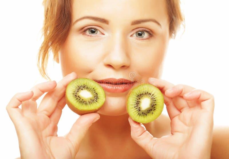 Gesunde Ernährung, Nahrung und Diätkonzept - bezaubernde junge Frau, die frische saftige Kiwi und Lächeln hält lizenzfreies stockbild