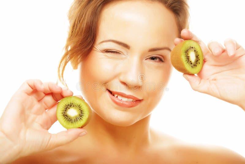 Gesunde Ernährung, Nahrung und Diätkonzept - bezaubernde junge Frau, die frische saftige Kiwi und Lächeln hält stockbilder