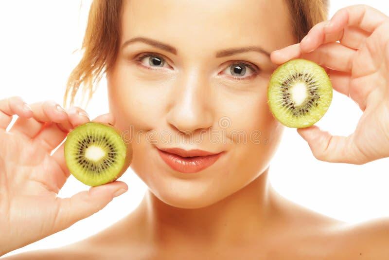 Gesunde Ernährung, Nahrung und Diätkonzept - bezaubernde junge Frau, die frische saftige Kiwi und Lächeln hält stockbild