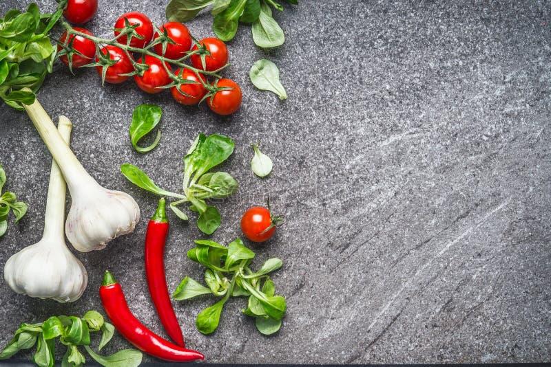 Gesunde Ernährung und Kochen mit frischen organischen Bestandteilen Kräuter, Gewürze, Tomaten, Salatblätter, Knoblauch und Paprik stockfoto