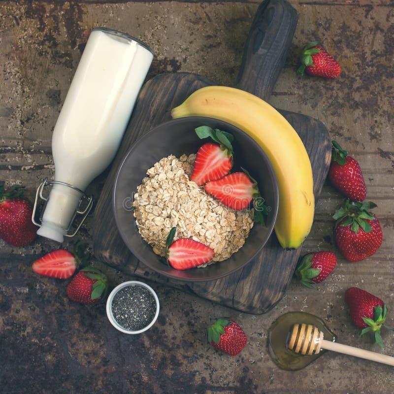 Gesunde Frühstücksbestandteile: Hafermehl, Honig, Frucht, Erdbeere lizenzfreies stockbild
