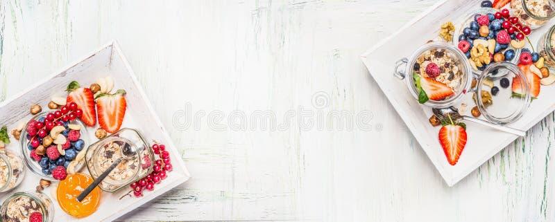 Gesunde Frühstücksbestandteile: Muesli im Glas mit frischen Beeren, Samen und Nüssen auf hellem hölzernem Hintergrund, Draufsicht lizenzfreie stockfotos