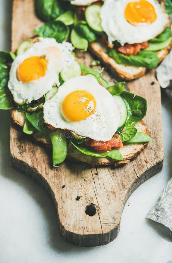 Gesunde Frühstückssandwiche auf hölzernem Brett über grauem Hintergrund lizenzfreie stockfotografie