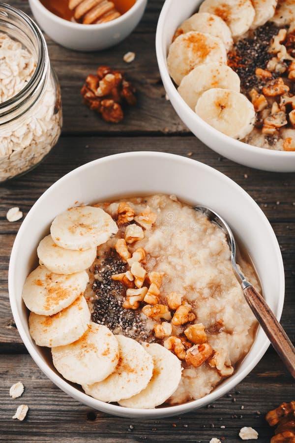 Gesunde Frühstücksschüssel Hafermehl mit Banane, Walnüssen, chia Samen und Honig stockfotos