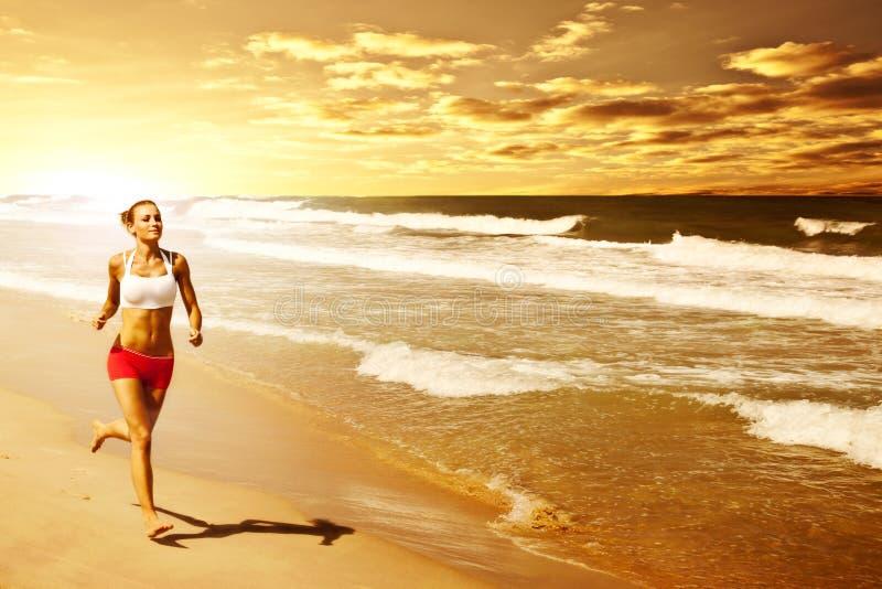 Gesunde Frau, die auf den Strand läuft lizenzfreies stockbild