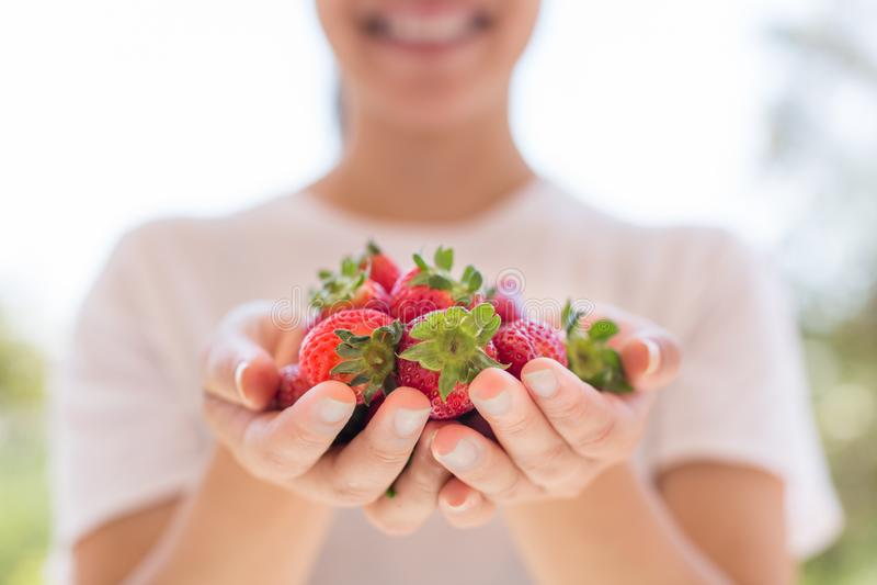 Gesunde Frau, die eine Handvoll Erdbeeren im Garten hält lizenzfreie stockbilder