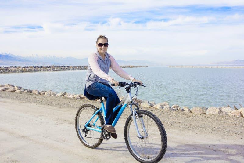 Gesunde Frau, die entlang die Ufergegend radfährt stockfotografie