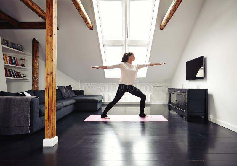 Gesunde Frau, die im Wohnzimmer trainiert stockfoto