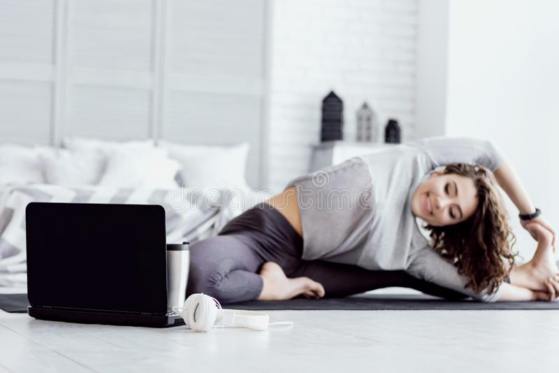 Gesunde Frau, die zu Hause Yogatraining tut stockfotos