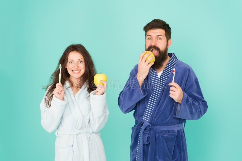 Gesunde Gewohnheiten B?rstenz?hne jeden Morgen Mundhygiene Paarbadem?ntel halten Zahnb?rsten und ?pfel Pers?nliche Hygiene lizenzfreie stockfotografie