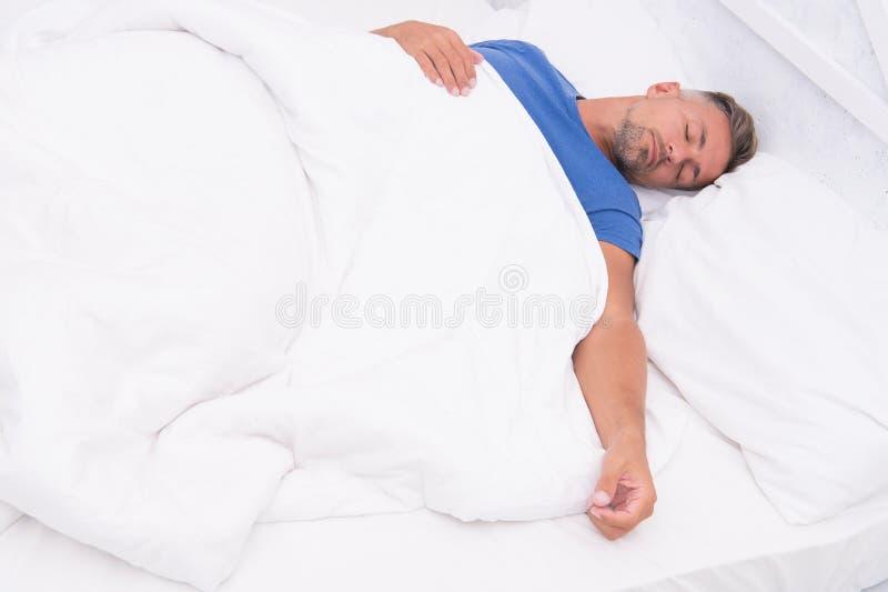 Gesunde Gewohnheiten Hübscher Kerl des Mannes legen beim Bettschlafen Erhalten Sie genügend Menge Schlaf Spitzenschlafen besser B lizenzfreies stockfoto