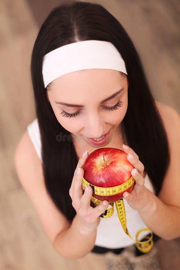 Gesunde glückliche Frau mit Apfel und Maßband für Diät- und Gewichtsverlustkonzept lizenzfreie stockfotografie