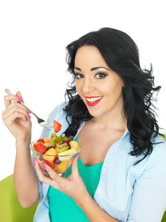 Gesunde glückliche frische gegenübergestellte junge Frau, die einen frischen Obstsalat isst lizenzfreies stockfoto