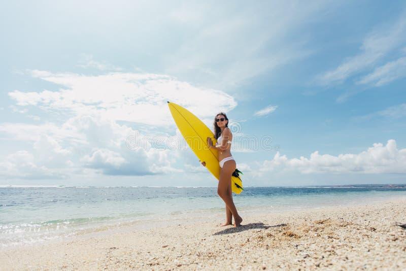 Gesunde glückliche schöne sexy Frau mit dem Surfbrett, das Spaß durch Meer auf Hintergrund des blauen Himmels hat Aktive Lebensst stockfotografie