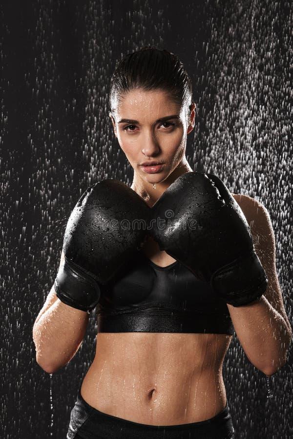 Gesunde gymnastische Frau, die in den Handschuhen und in der Stellung in ATT kickboxing ist lizenzfreies stockfoto
