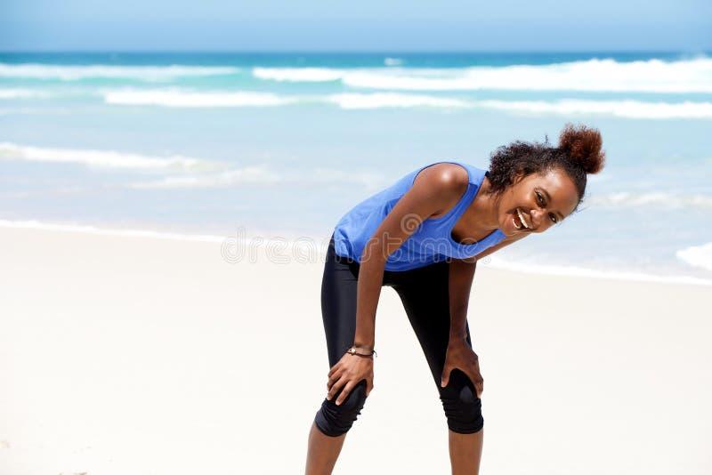 Gesunde junge afrikanische Frau, die über den Strand lacht stockfotografie