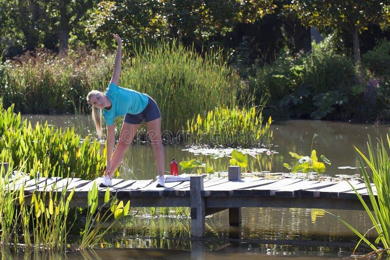 Gesunde junge blonde Frau, die ihre Arme unten über Wasser ausdehnt lizenzfreie stockfotos