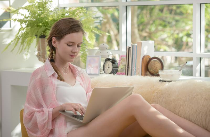 Gesunde junge Frau, die auf einer Couch unter Verwendung der Laptop-Computers schaut entspannt und bequem sitzt lizenzfreie stockfotografie