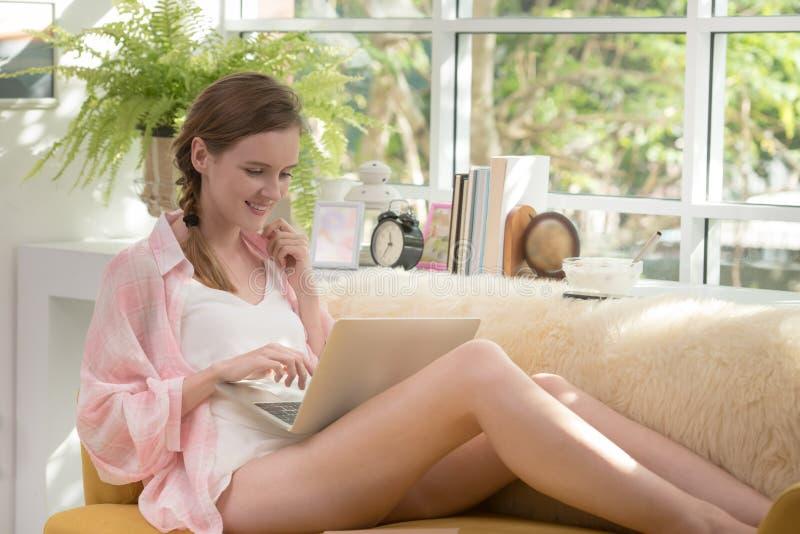 Gesunde junge Frau, die auf einer Couch unter Verwendung der Laptop-Computers schaut entspannt und bequem sitzt lizenzfreies stockbild