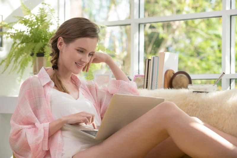 Gesunde junge Frau, die auf einer Couch unter Verwendung der Laptop-Computers schaut entspannt und bequem sitzt stockfoto