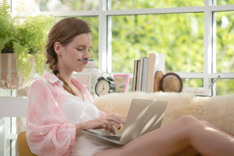 Gesunde junge Frau, die auf einer Couch unter Verwendung der Laptop-Computers schaut entspannt und bequem sitzt stockfotografie