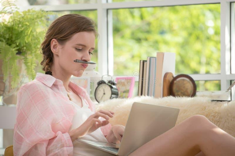 Gesunde junge Frau, die auf einer Couch unter Verwendung der Laptop-Computers schaut entspannt und bequem sitzt stockbilder