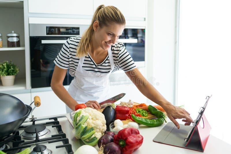 Gesunde junge Frau, die Frischgemüse schneidet und zu Hause digitale Tablette zu den Rezepten in der Küche verwendet stockfotografie