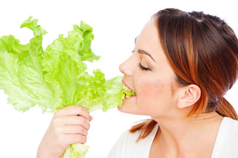 Gesunde junge Frau, die grünen Kopfsalat isst stockfoto