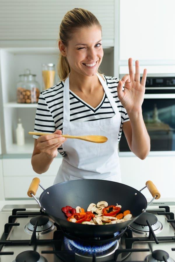 Gesunde junge Frau, die Kamera beim Nahrung in der Bratpfanne in der Küche zu Hause kochen und mischen betrachtet lizenzfreie stockbilder