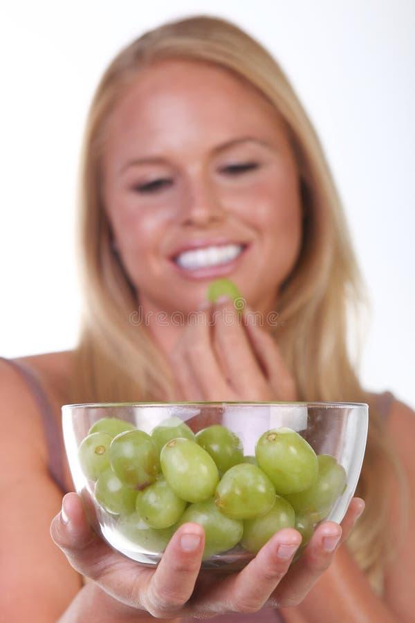 Gesunde junge Frau, die nahrhafte Nahrung isst lizenzfreie stockbilder