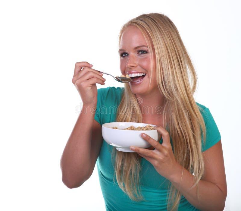 Gesunde junge Frau, die nahrhafte Nahrung isst stockbild