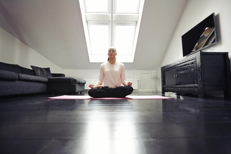 Gesunde junge Frau, die zu Hause meditiert lizenzfreie stockbilder