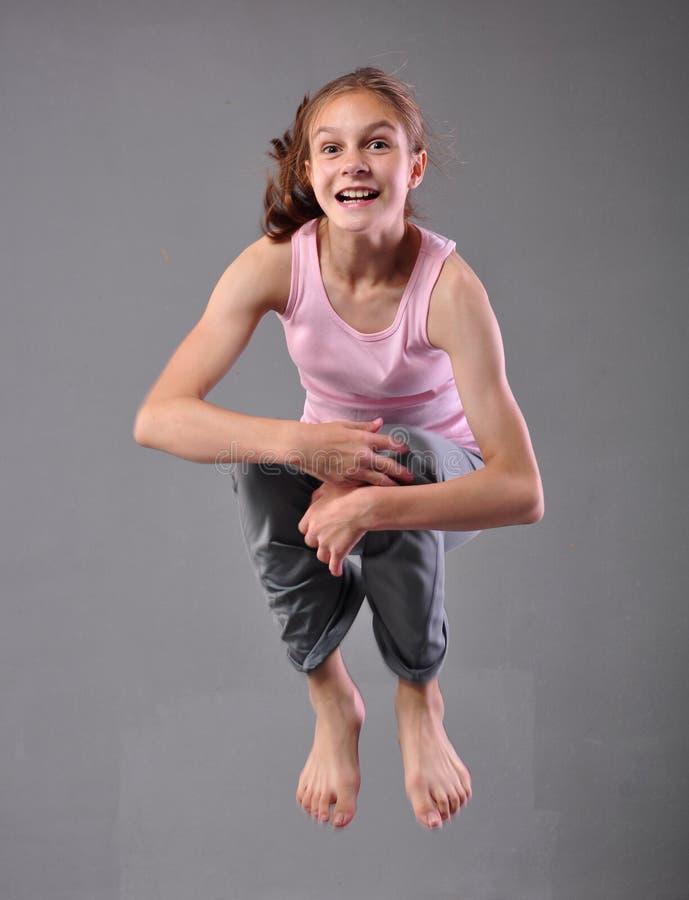 Gesunde junge glückliche lächelnde Jugendliche, die in Studio überspringt und tanzt Kind, das mit dem Springen auf grauen Hinterg lizenzfreie stockfotografie