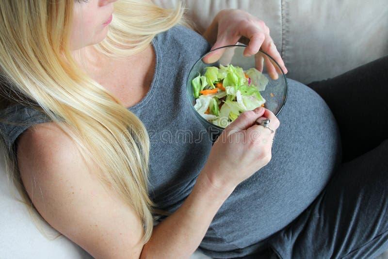 Gesunde, junge, schwangere Frau, die auf der Couch isst grünen Kopfsalat-Salat sitzt lizenzfreie stockbilder
