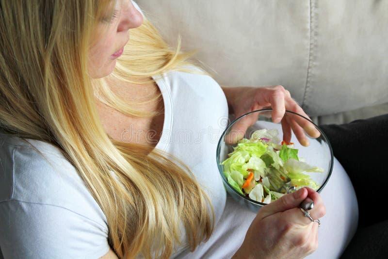 Gesunde junge schwangere Frau, die einen grünen Blatt-Salat isst lizenzfreie stockfotografie