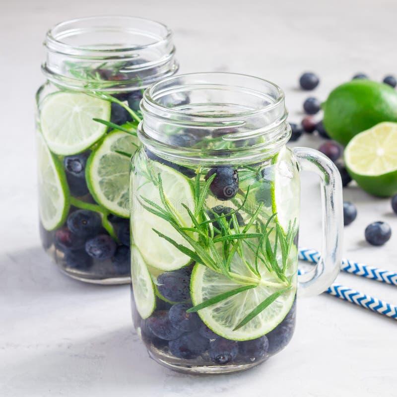 Gesunde Kälte goss Wasser mit frischer Blaubeere, Kalk und Rosmarin, Quadrat hinein lizenzfreie stockbilder