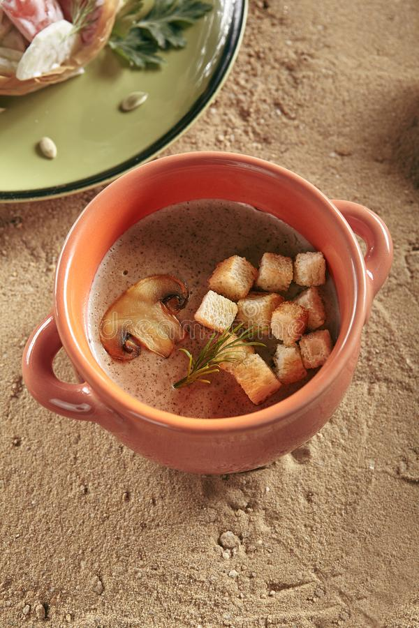 Gesunde Kindernahrung mit Pilzen sahnen Suppe im natürlichen keramischen Topf stockbilder