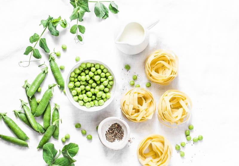 Gesunde Lebensmittelinhaltsstoffe der Mittelmeerart für das Mittagessen zurück kochen - Fettuccineteigwaren, frische grüne Erbsen lizenzfreies stockbild