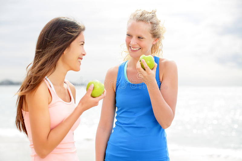 Gesunde Lebensstilfrauen, die Apfel nachdem dem Laufen essen lizenzfreie stockbilder