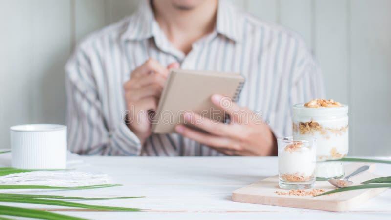 Gesunde Mahlzeit des ausgewählten Fokus gemacht vom Granola im Glas mit asiatischem männlichem Schreiben der Unschärfe auf Notizb lizenzfreie stockfotografie