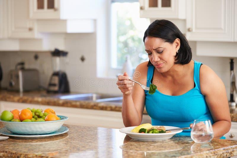 Gesunde Mahlzeit Fed Up Overweight Woman Eatings in der Küche lizenzfreie stockbilder