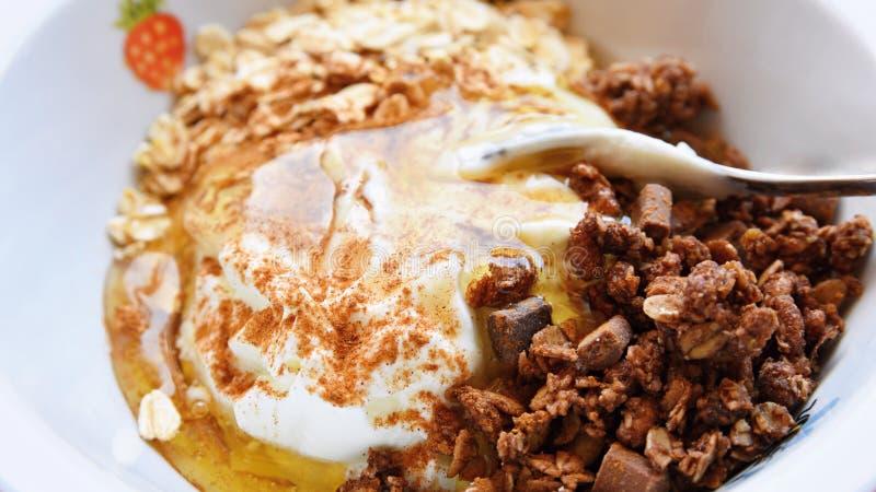 Gesunde Nahrung - Frühstück in einem weißen Teller Muesli, Jogurt, Hafermehl mit Schokolade, Honig und Zimt stockbild