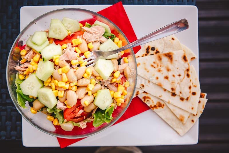 Gesunde Nahrung Geschmackvoller Fischsalat mit Thunfischen, Kopfsalat, Bohnen, Mais, Gurke und Tomaten in einer Platte mit Gabel  lizenzfreie stockfotografie