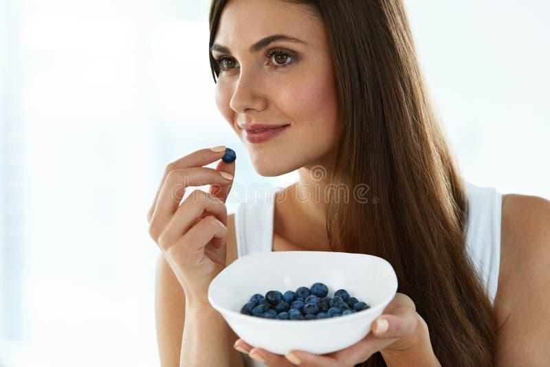 Gesunde Nahrung Glückliche Frau auf Diät organische Blaubeeren essend stockfotos
