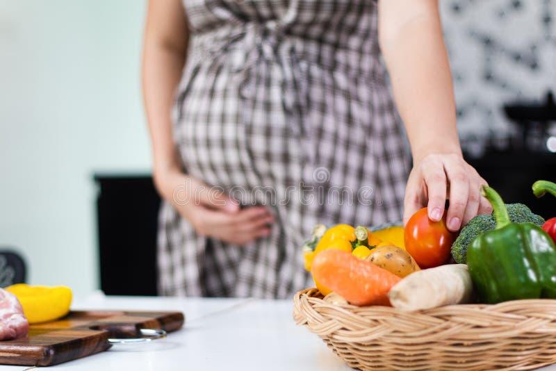 Gesunde Nahrungsmittel für schwangere Frauen, junge schwangere Frau, die frische Tomate nimmt lizenzfreies stockbild