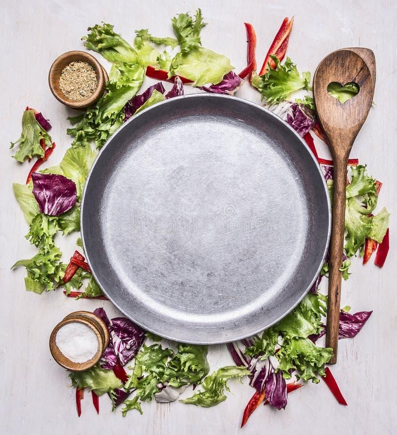 Gesunde Nahrungsmittel, Kochen und vegetarischer Konzeptkopfsalat mit einem hölzernen Löffel, einem Salz und einem Pfeffer, ausge stockfoto
